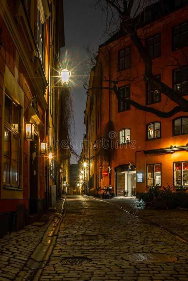 Old cobbled narrow street in Stockholm at night royalty free stock photo