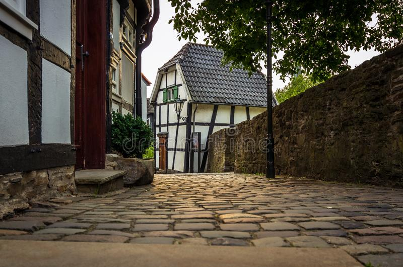 Old cobblestone alley, half-timbered houses on the left and a stone wall right on the edge of the picture, Hattingen royalty free stock image