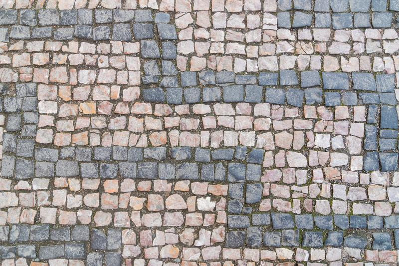 Old cobblestone pattern, stone textured background, gray and pinky granite stones royalty free stock photo