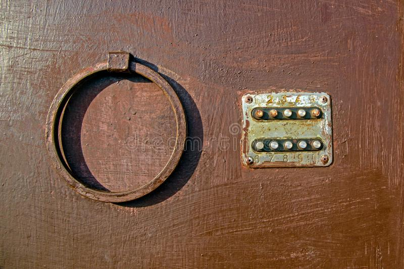 Old coded lock with round buttons on the iron door, close-up, old painted door, lock. Texture of paint on metal royalty free stock photo