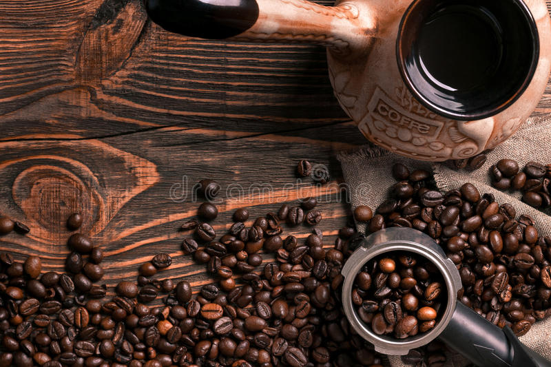 Old coffee cup and turk with roasted beans on a wooden table. stock images