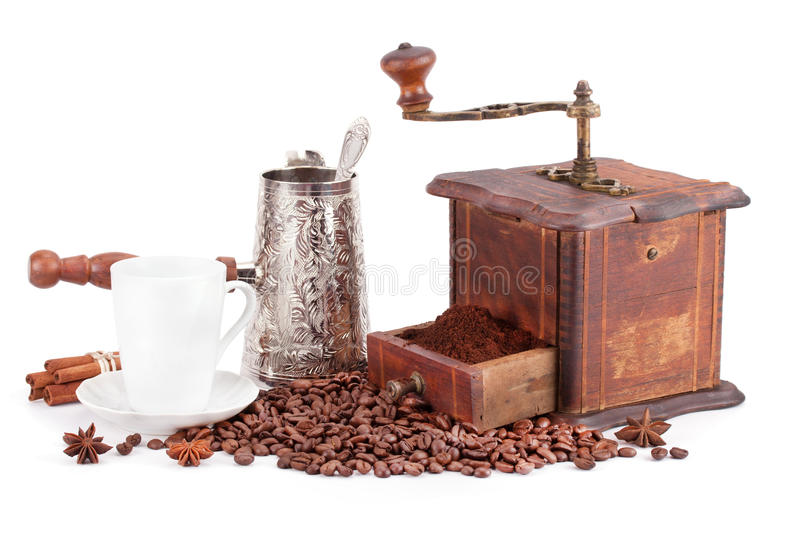 Old coffee grinder, kettle and cup of coffee. Old coffee grinder, kettle and cup of coffee isolated on white background royalty free stock photography