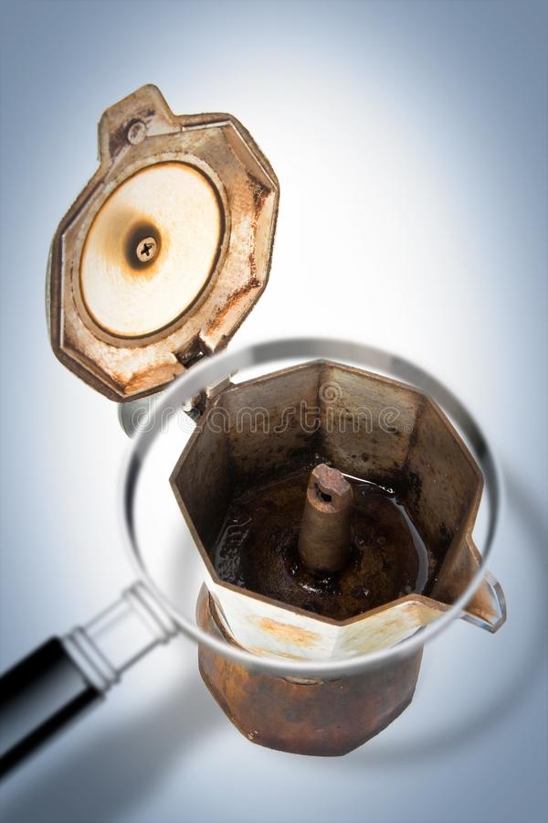 Old coffee maker called `moka` or `mocha` for italian coffee espresso with open lid seen through a magnifying glass - Concept im. Age royalty free stock images