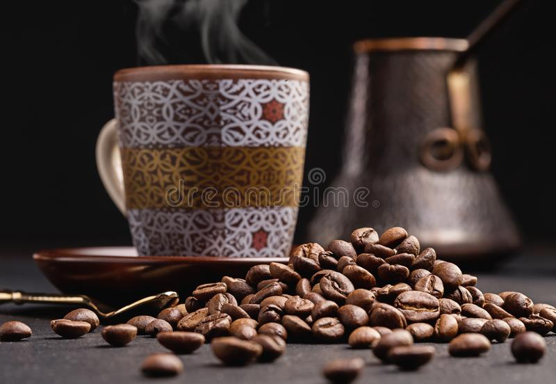 Old coffee pot, coffee beans and cup of hot coffee. royalty free stock image