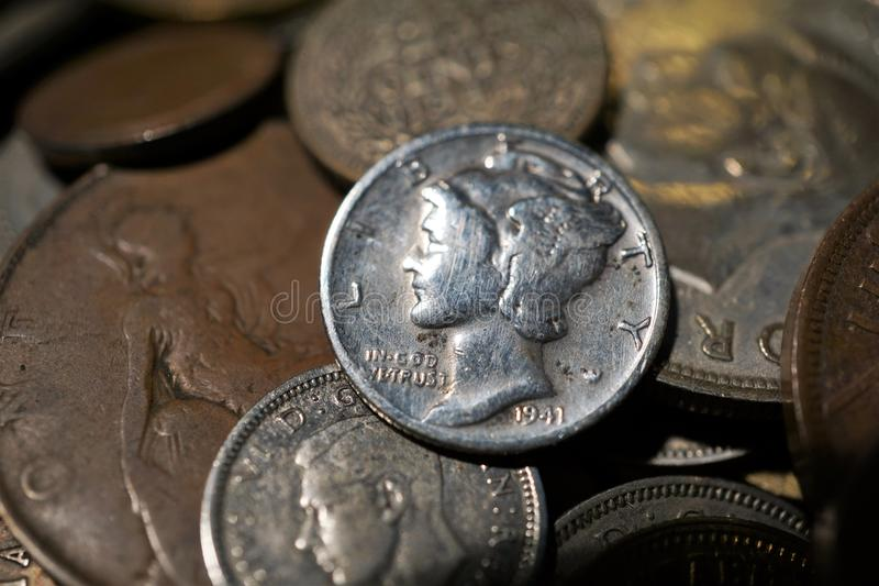 Old coins. A pile of old coins with a silver liberty dime on top stock photo