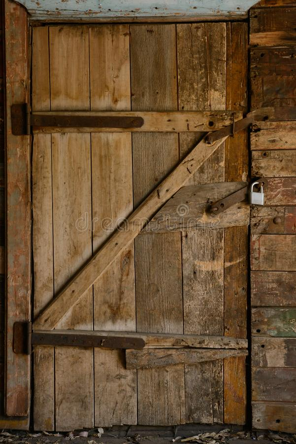 Old collapsing wooden door with rusty hinges royalty free stock images