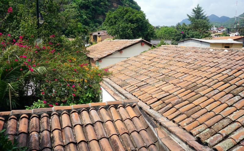 Old colonial houses roofs. Mexican colonial houses build it in the middle of a rainy woods, roof tiles in baked clay orange color, roofs stained by the weather stock photos