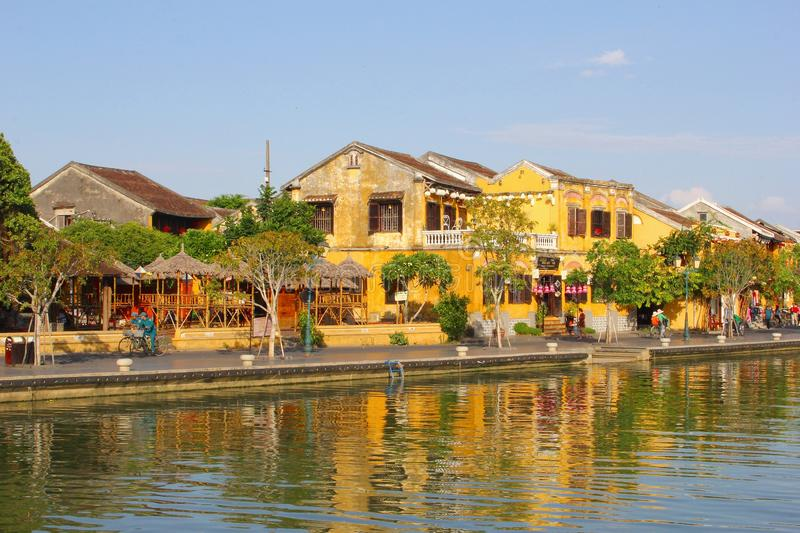 Yellow historic buildings river reflections, Hoi An. Old colonial yellow buildings along the river and reflections in water white people are cycling and walking stock photos