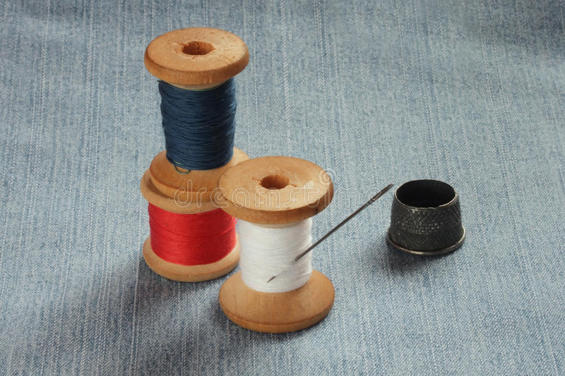 Old colored spools of thread. And metal thimbles royalty free stock photos