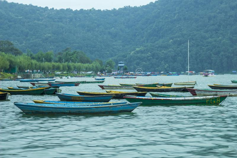 A old colored wooden boats and a sailboat on the lake against the backdrop of green mountains in the evening stock photos