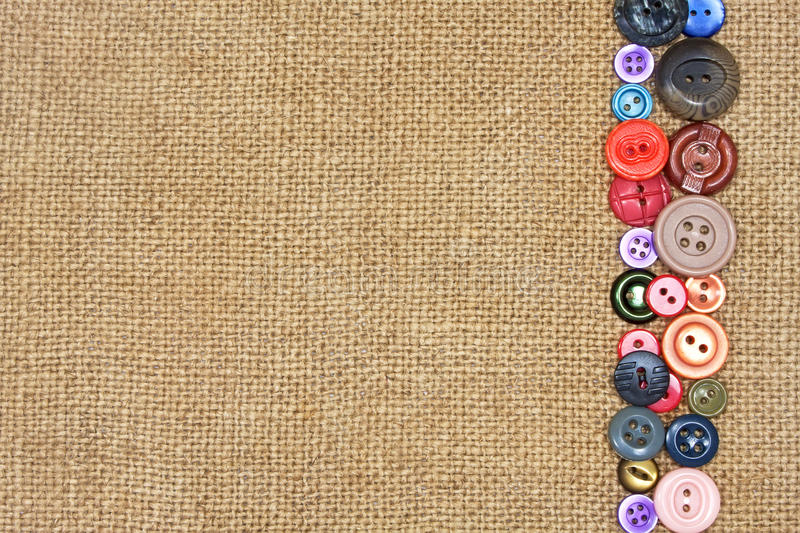 Old colorful buttons on burlap. Old colorful buttons on the background burlap stock photo