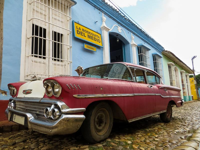 Old colorful Cuban car on cobblestone street royalty free stock photos