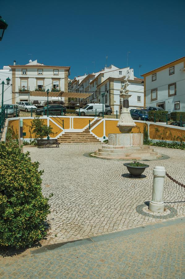 Old colorful houses around square with marble statue. Charming marble statue in the center of cobblestone square and colorful houses around it at Castelo de Vide stock photo