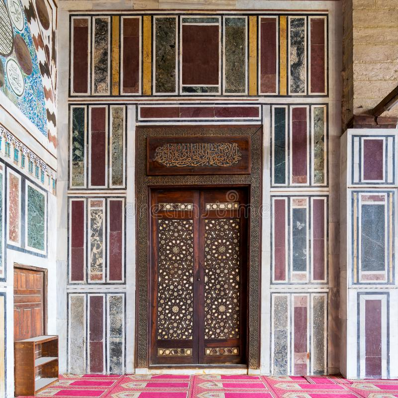 Old colorful marble wall with wooden door decorated with arabesque ornaments, Cairo, Egypt. Old colorful marble wall with wooden door decorated with arabesque royalty free stock photo