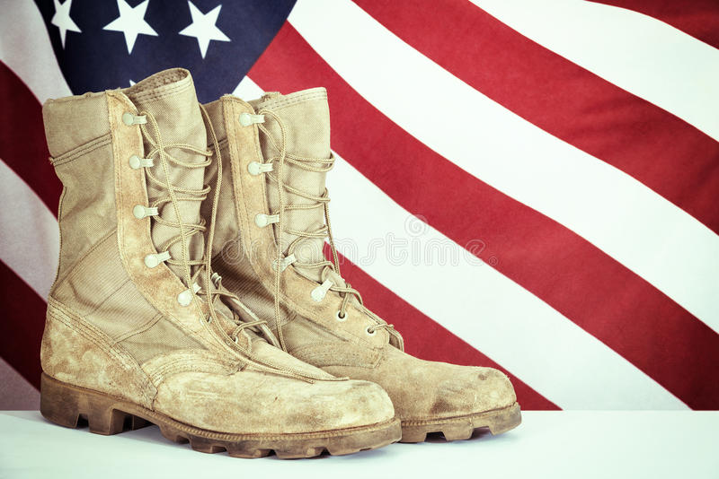 Old combat boots with American flag. In the background. Vintage filter effect stock photos