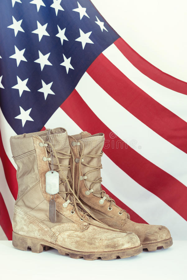 Old combat boots and dog tags with American flag stock images