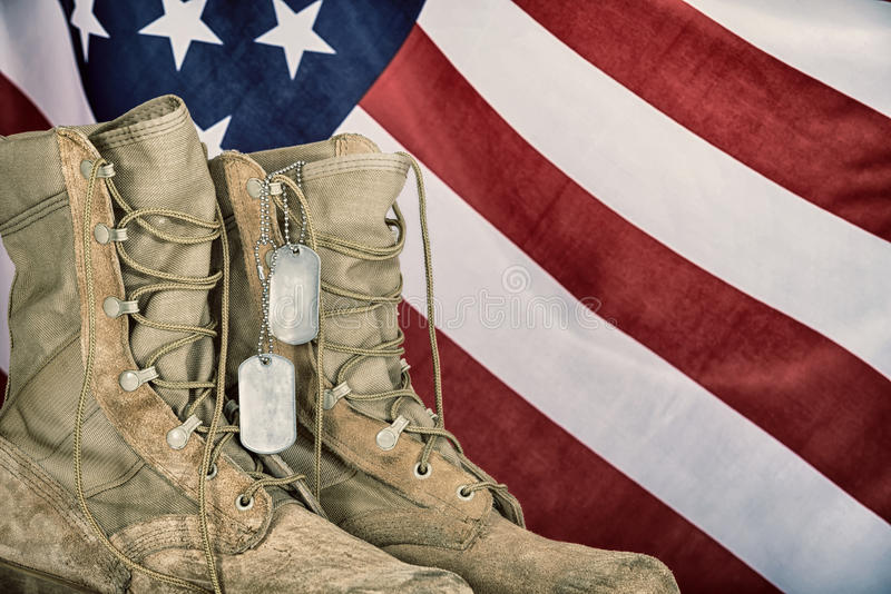 Old combat boots and dog tags with American flag. In the background. Vintage filter effects royalty free stock image