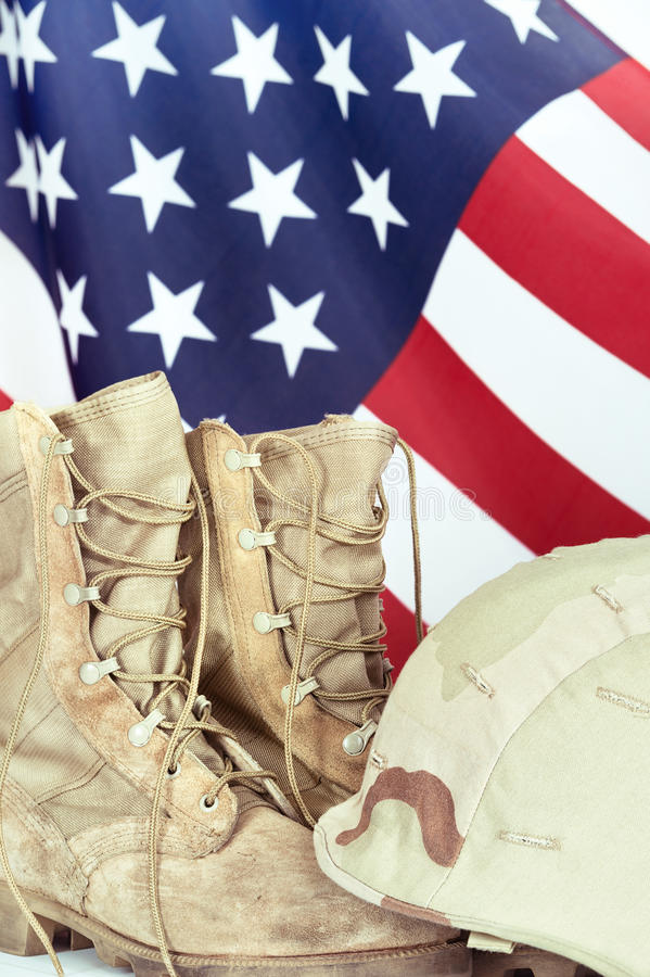 Old combat boots and helmet with American flag. In the background, closeup stock photography