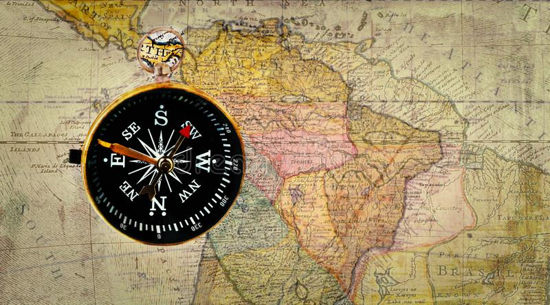 Old compass on antique cracked world map. Vintage still life. Top view stock photos