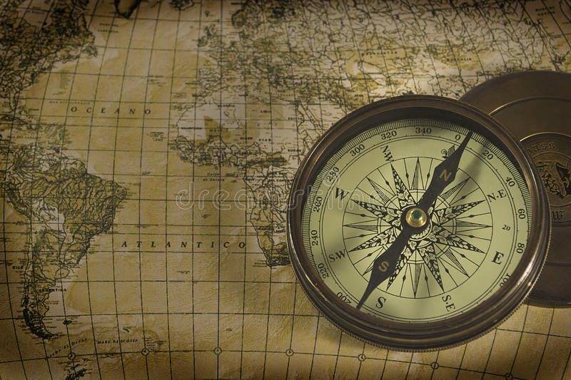 Old compass over map. Old brass compass over antique map