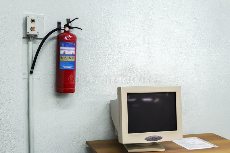 Old computer and a fire extinguisher on the wall stock image