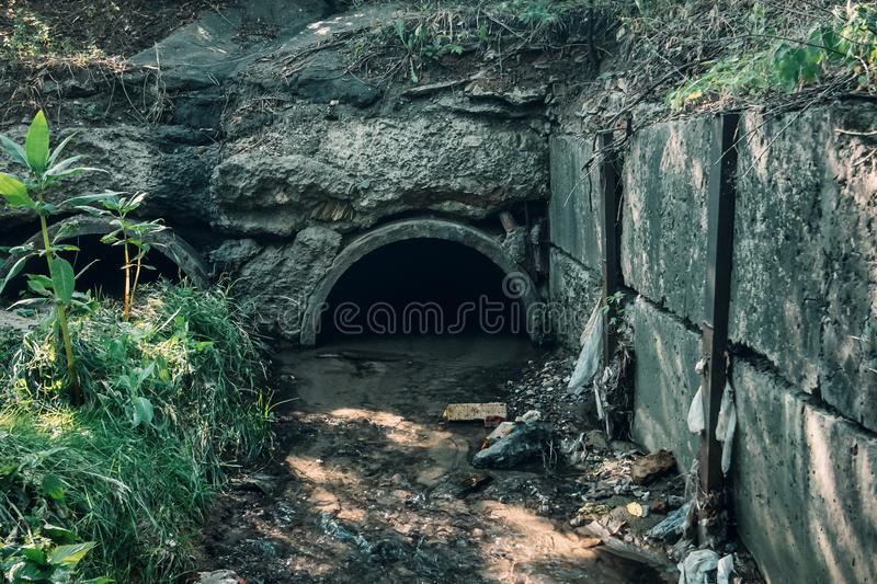 Old concrete drainage pipes with flowing wastewater, sewage or sewerage tunnel tube with water stream stock images