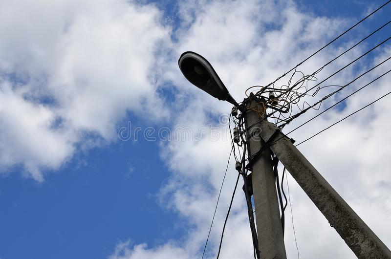 Old concrete electric pole for transmission of wired electricity with lamp post on a background of a cloudy blue sky. Obsolete me royalty free stock photo