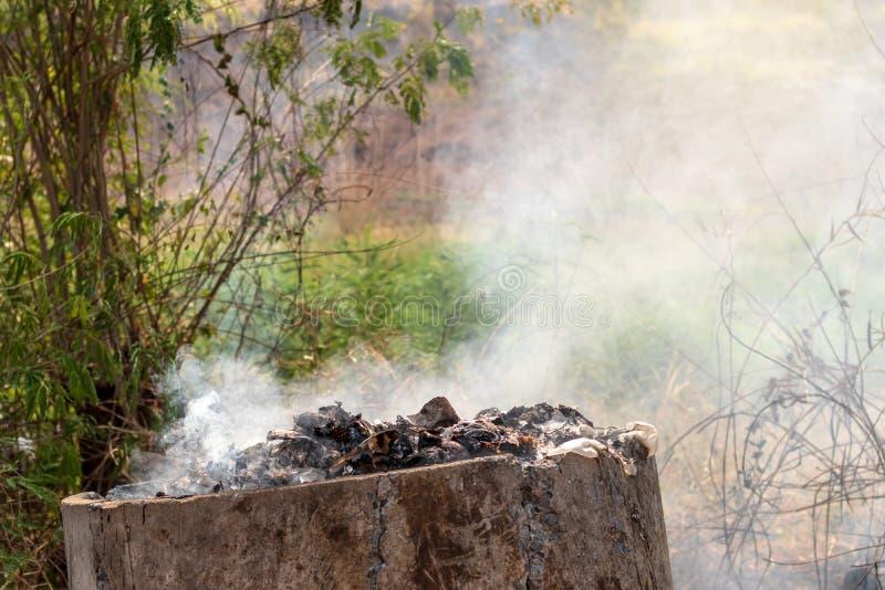 Old concrete tanks burn waste, causing smoke stock photo