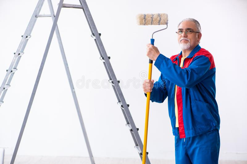 Old contractor doing renovation at home. The old contractor doing renovation at home royalty free stock photos
