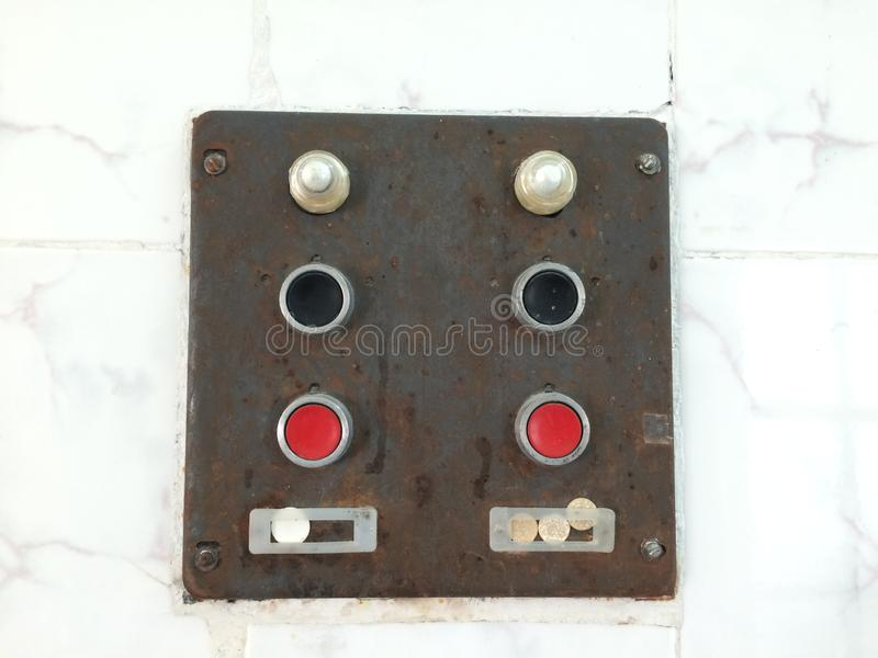 Old control unit with red and black buttons. Iron rusty board with mass switch and current supply royalty free stock photo