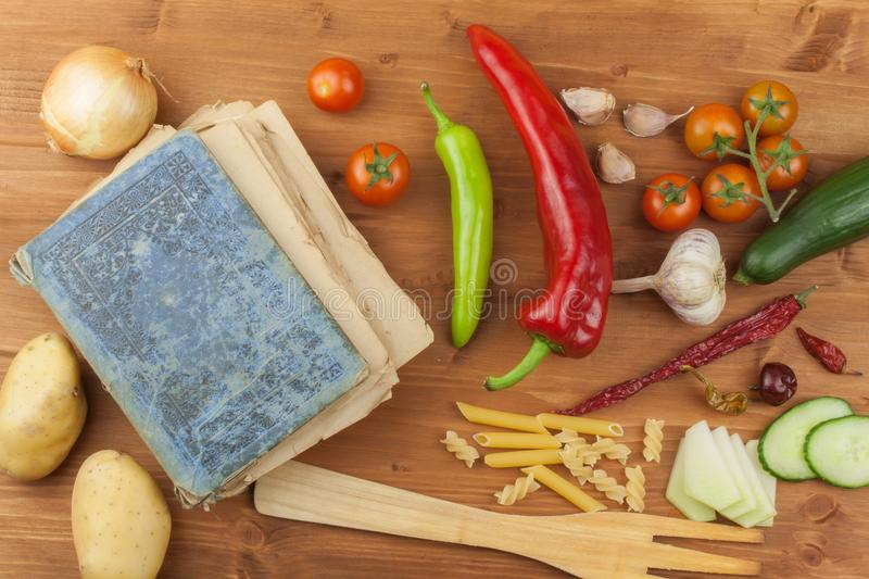 Old cookbook recipes on a wooden table. Cook healthy vegetable. Preparation of home diet food. Different kinds of vegetables royalty free stock photo