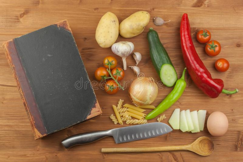 Old cookbook recipes on a wooden table. Cook healthy vegetable. Preparation of home diet food. Different kinds of vegetables royalty free stock photos