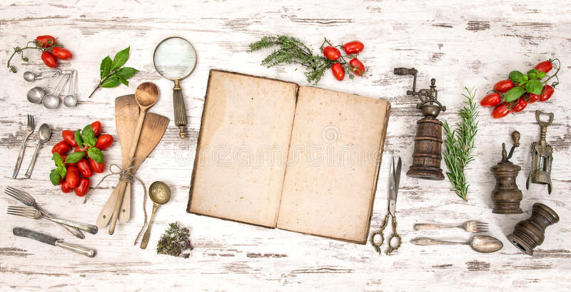 Old cookbook with vegetables, herbs and vintage kitchen utensils. Retro style toned picture royalty free stock photos