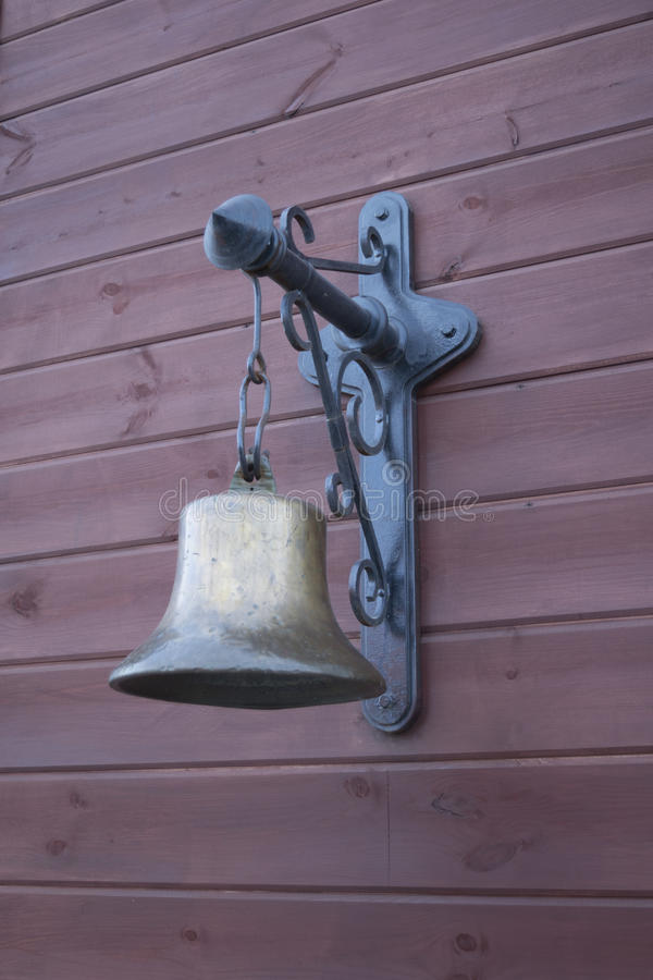 Old copper bell on a wooden facade royalty free stock images