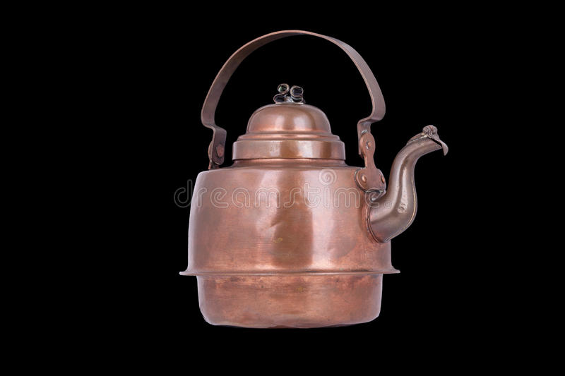 Old copper kettle isolated on a black background. An old copper kettle isolated on a black background stock images