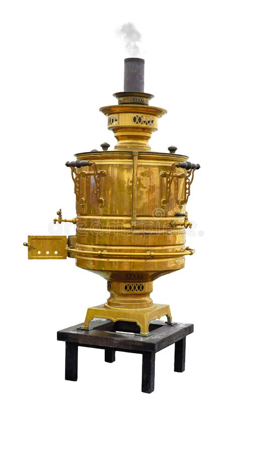 Old copper samovar with a chimney from which smoke comes stands on a small table isolated on a white background. An old copper samovar with a chimney from which stock photos