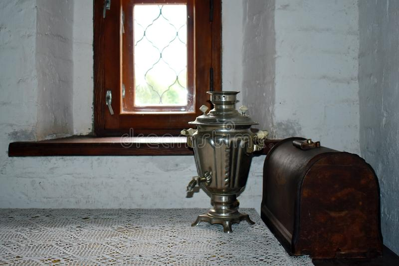 Old copper samovar and wooden chest at window in the room stock photo