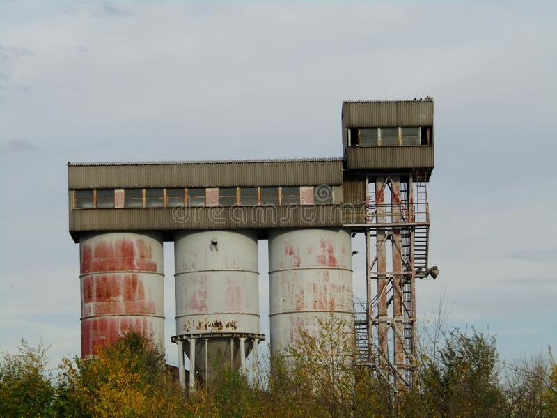 Old and corroded abandoned silo. In the old and abandoned industrial zone stock photography