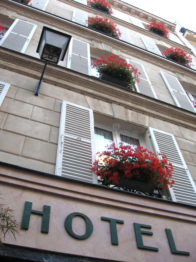 Old cosy hotel. With flowers at the windows stock photography