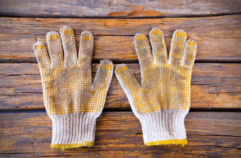 Old cotton work glove. Cotton work gloves.Cotton knitted work gloves lying in the wood background royalty free stock photography