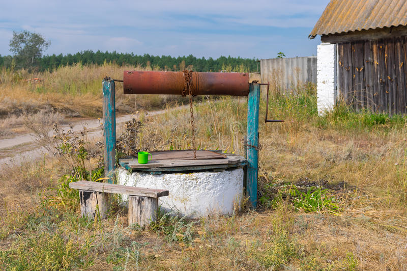 Old country draw-well with wooden bench at. In central Ukraine stock images