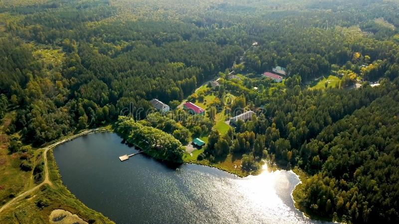 Old country resort in forest by lake. Stock footage. Top view of picturesque recreation center located by lake royalty free stock photo