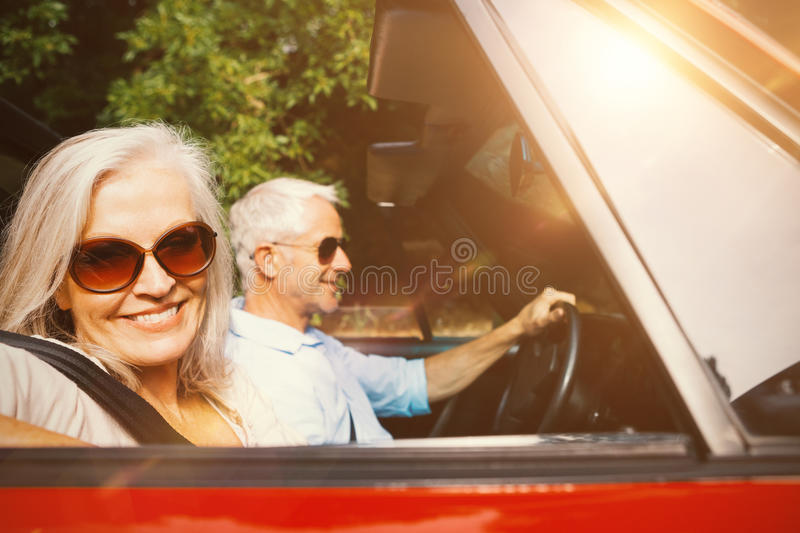 Old couple in a car smiling at camera royalty free stock photos