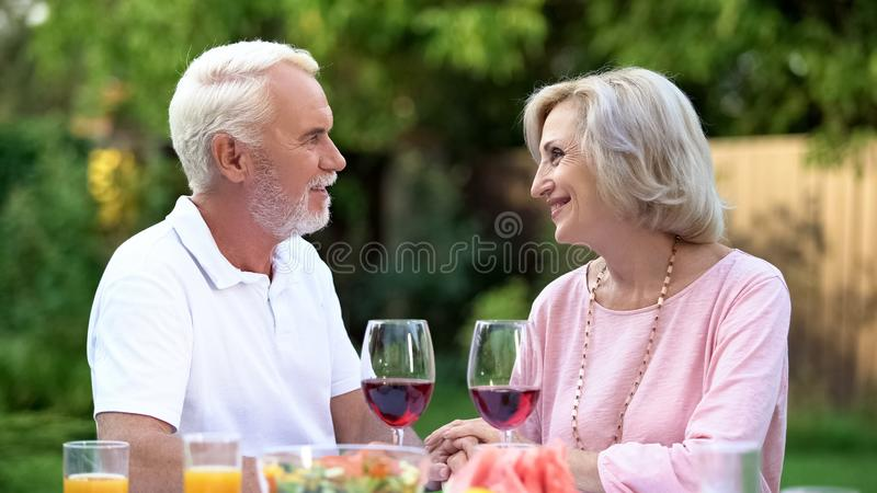 Old couple celebrating anniversary, drinking wine, everlasting love relations stock photos