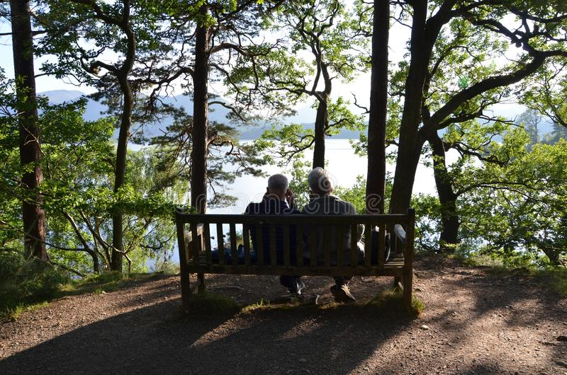 Old couple enjoying the view at lake windermere in the lake district. Cumbria, england, united kingdom royalty free stock photo