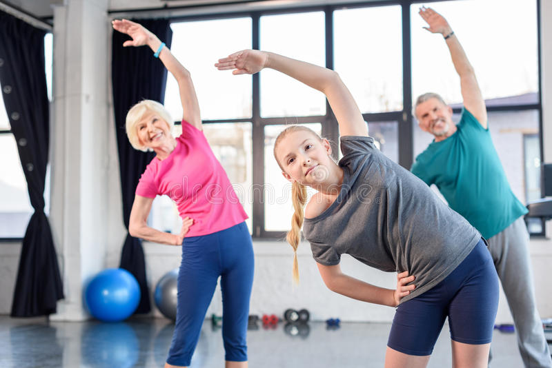 Old couple and girl exercising in fitness class for kids and senior people. Happy old couple and girl exercising in fitness class for kids and senior people royalty free stock photo