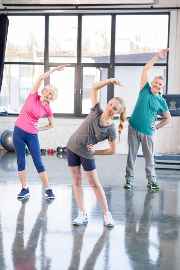 Old couple and girl in sportswear exercising in fitness class for kids and senior people. Happy old couple and girl in sportswear exercising in fitness class for stock image