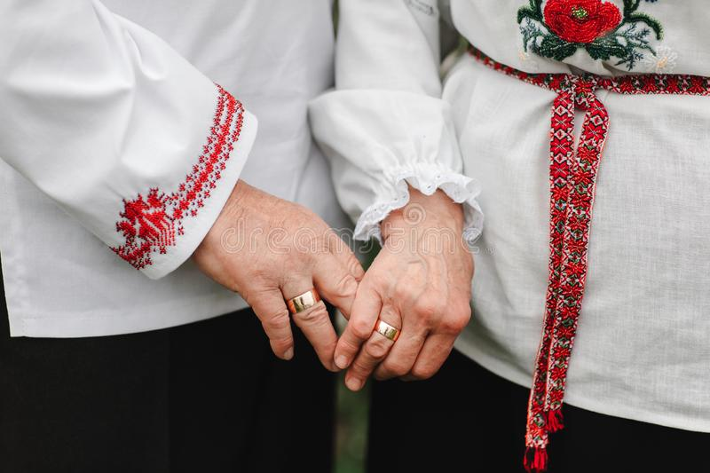 The old couple is holding hands. Close up of senior man and woman holding hands and walking outdoors stock image