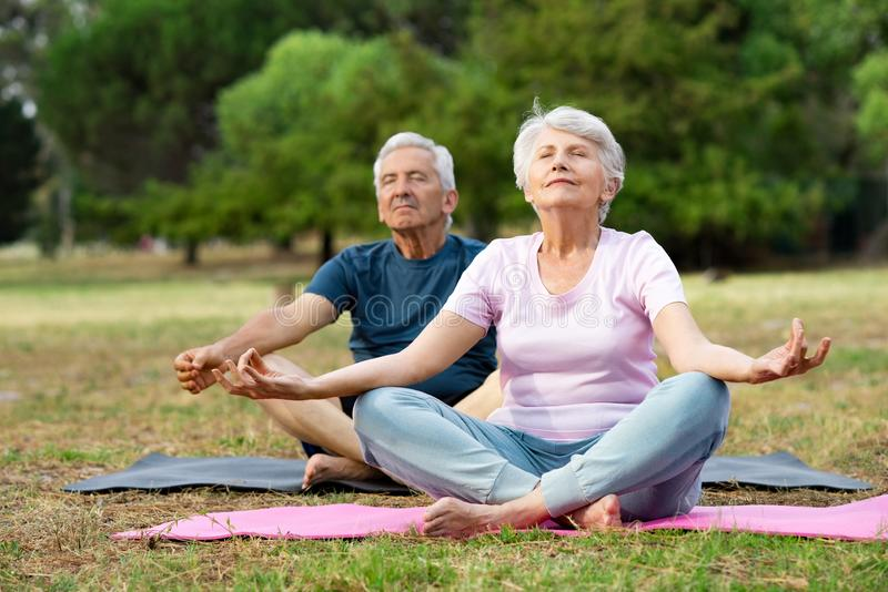 Senior couple doing yoga stock photography