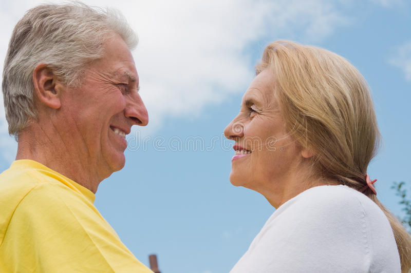Old couple with sky. Portrait of a cute old couple with sky royalty free stock photo